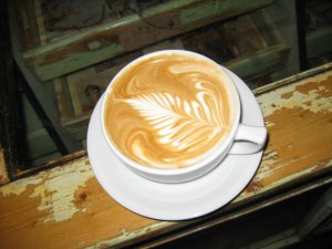 A beautiful latte sitting on the counter, an antique store display case