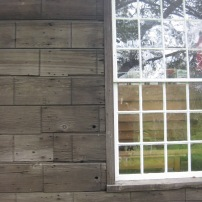 Wood clapboards etched to look like stone blocks rather than wood boards. This 12/12 window has original panes, too. Taken at the Eureka Schoolhouse in Springfield, Vermont - a State Historic Site.