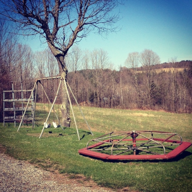 The playground has three apparatuses: jungle gym, swings, and a merry-go-round.