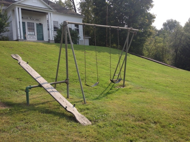 A swingset on the playground with a seesaw, swings, and steps to nowhere - probably previously to a slide.