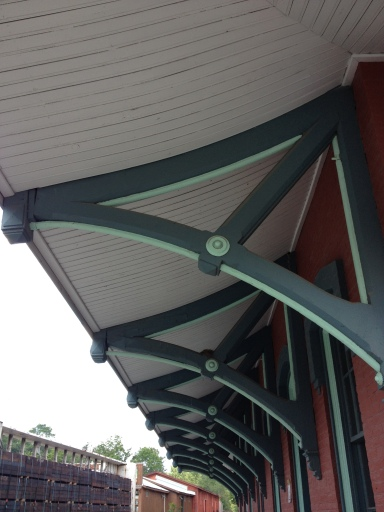Classic railroad station brackets underneath large overhanging, flared eaves. Chester Depot, VT.