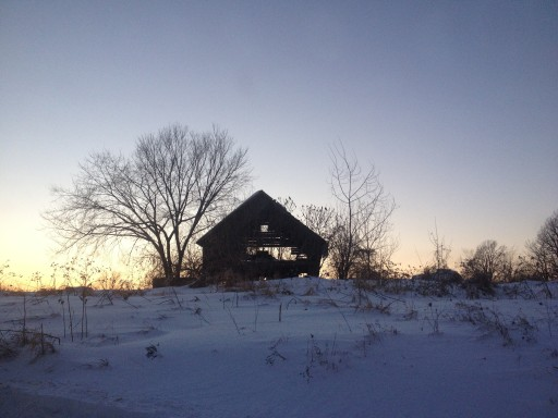 A barn on the verge of collapse with another snowfall sits peacefully watching the sunset.