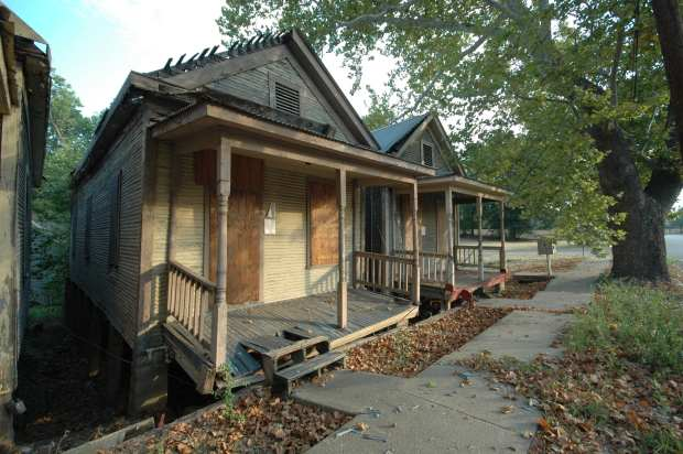 The shotgun houses, boarded up and awaiting this project.