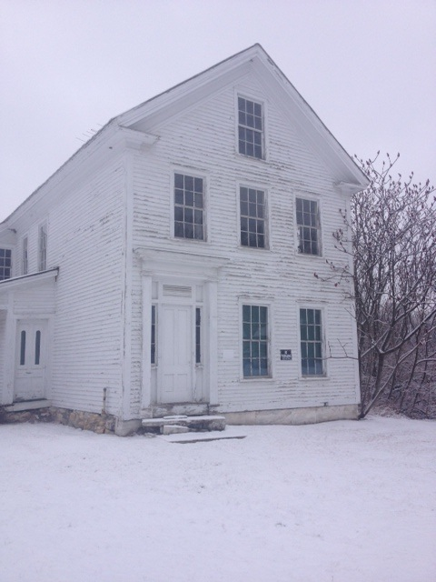 Brandon House.  White house in the white winter snow. The windows look dark and cold, and the house immediately seemed to have that abandoned lure.