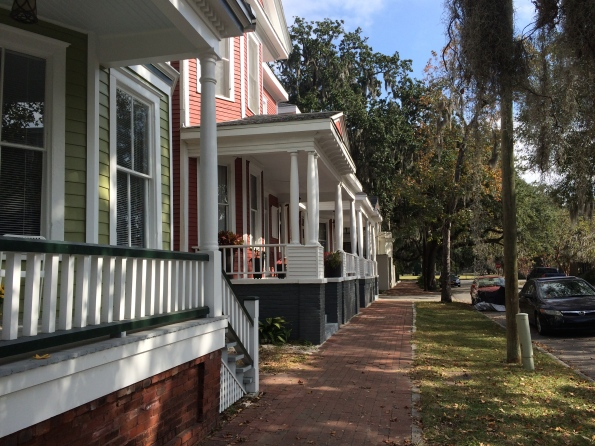 A street near Forsyth Park: porches, brick sidewalk, mature trees.