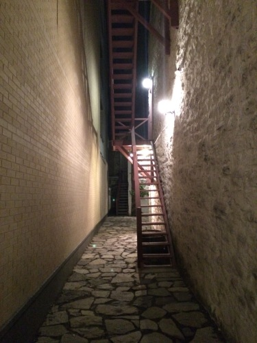 A stone walkway, red staircase, and a light: quite welcoming for an alley.