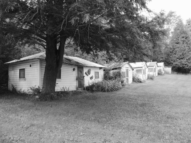 Tourist cabins in a row. The cabin in the foreground is larger, perhaps for the owner or for a larger family unit.